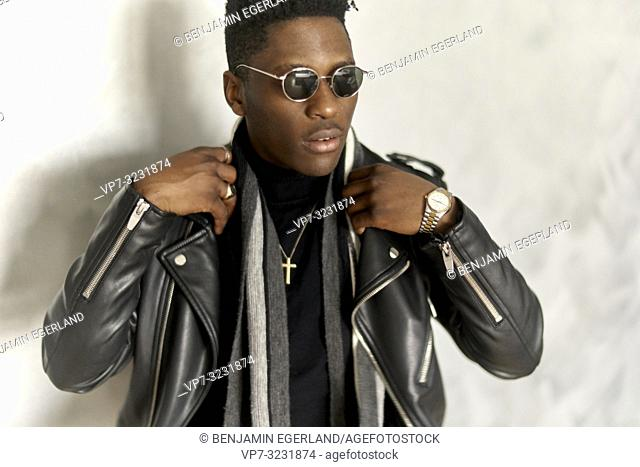 portrait of fashionable African man wearing christian cross necklace, sunglasses, scarf and leader jacket, in Munich, Germany
