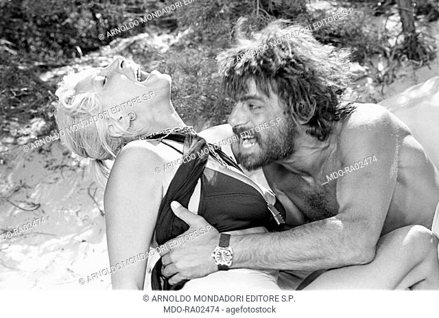 Italian actor, director and scriptwriter Giancarlo Giannini seizing Italian actress Mariangela Melato in the film Swept away. Italy, 1974