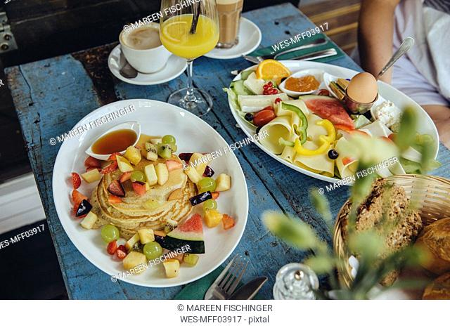 Plates with pancakes and fruit and vegetarian breakfast at cafe