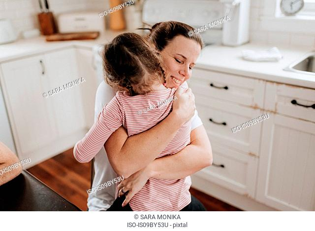 Mother hugging daughter in kitchen