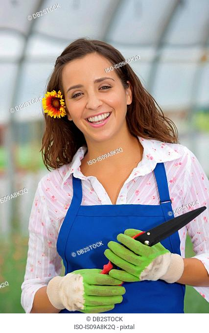 Young woman holding pruning shears in garden centre, portrait