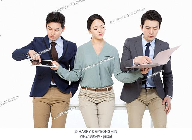 Smiling business woman holds out a tablet and file to her coworkers and they touch them