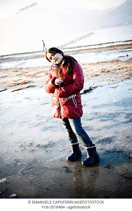 Portrait of little girl in winter beach, Ispra, Lake Maggiore, Italy