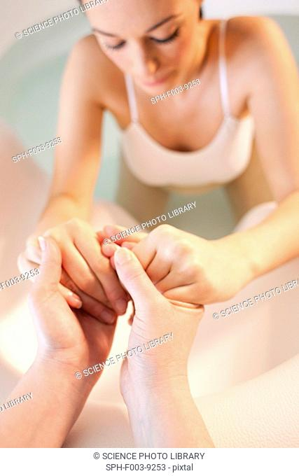 Water birth. Midwife holding the hands of a pregnant woman who is in a birthing pool