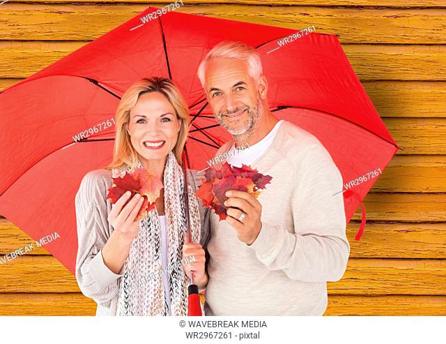 couple with umbrella with yellow wood background