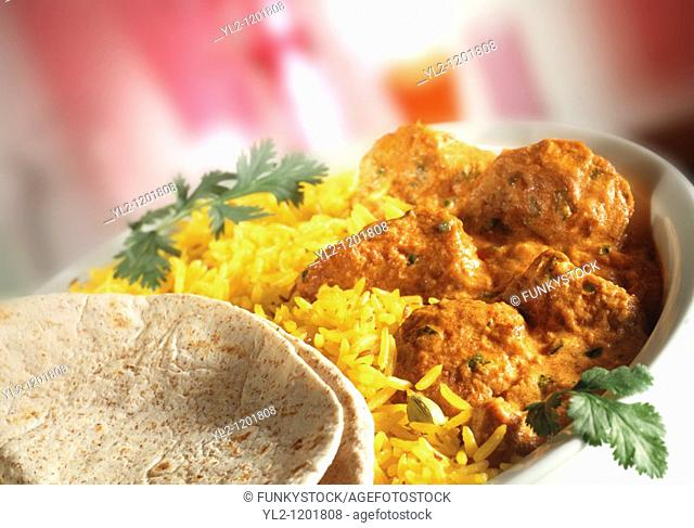 Chicken Madras - Pilau rice & naan bread in white dish with red background