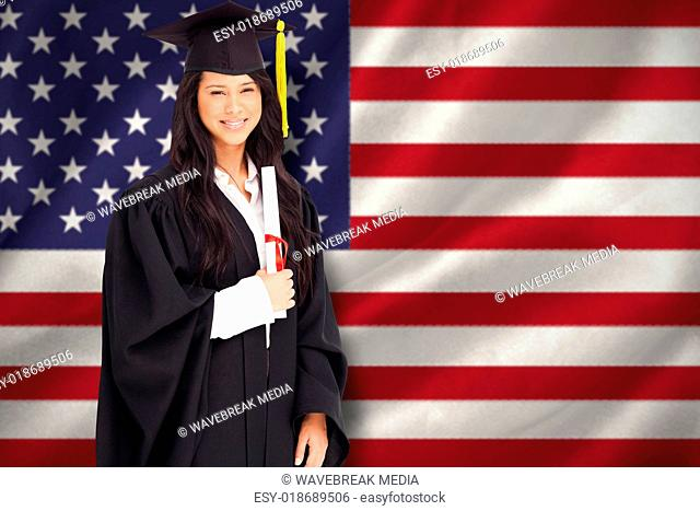 Composite image of a smiling woman holding her degree as she has graduated from university