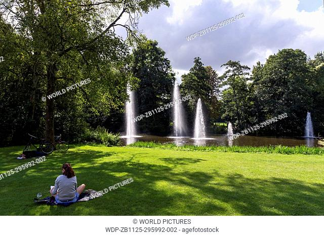 Young girl relaxing on grass on a sunny summer's day in Vondelpark, with fountains and pond, Amsterdam, Netherlands, Europe
