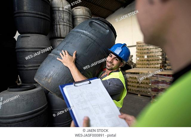 Workers make barrels inventory in warehouse