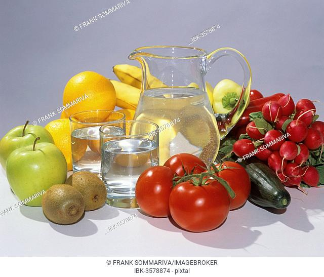 Glass carafe filled with water, two glasses, fruit and vegetables