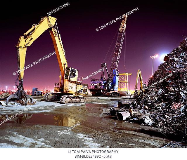 Mechanical grabber in junkyard at night