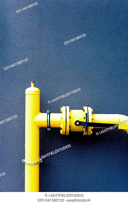 Yellow gas pipe in front of a blue wall