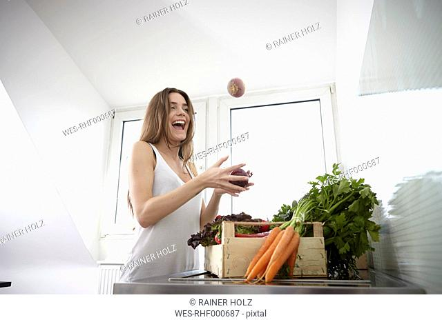 Happy young woman in kitchen with crate full of fresh vegetables