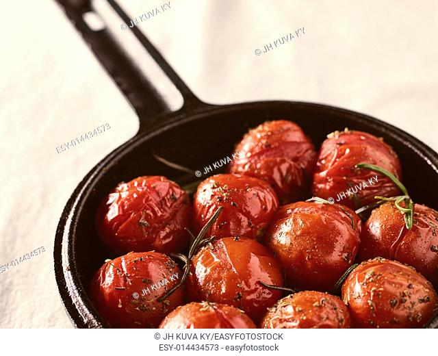 Grilled cherry tomatoes in a small cast iron pot, rosemary, horizon image