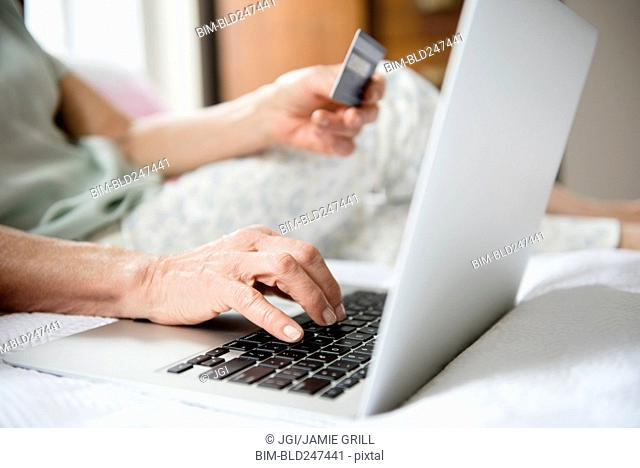 Hands of older woman shopping online with credit card and laptop