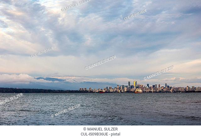 Distant view of city skyline over Vancouver harbour, Vancouver, Canada