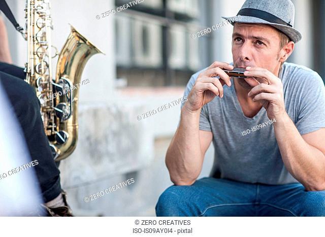 Street musician playing harmonica