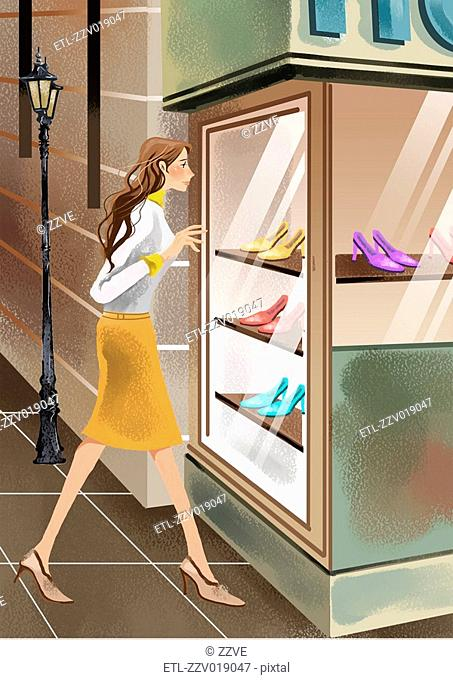 Side view of young woman looking at shoes in window of retail store