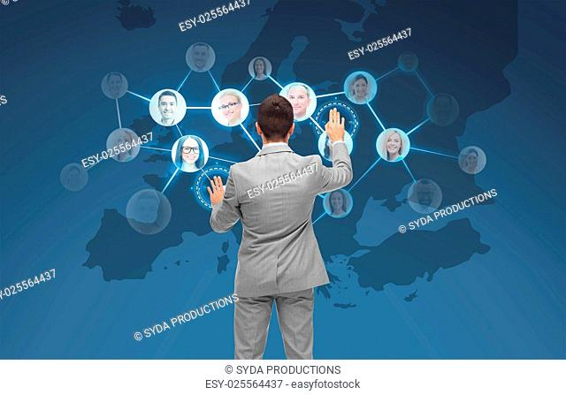 business, people, communication, cooperation and technology concept - businessman touching virtual screen with contacts icons and europe map over blue...