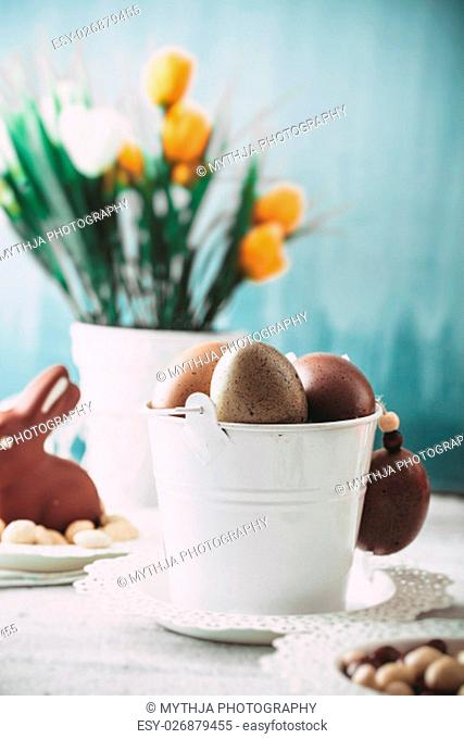 Easter. Chocolate Eggs and bunny on Easter table. Tulips in vase. Easter setting on table