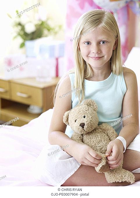 Girl in hospital with teddy bear smiling