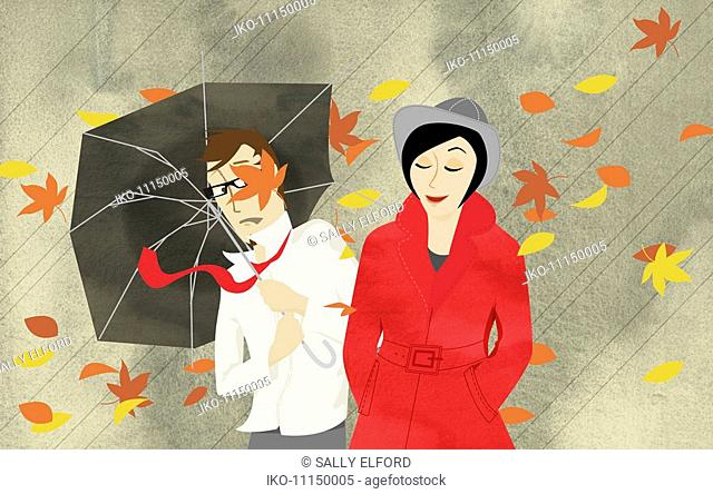 Wind blowing autumn leaves around man and woman