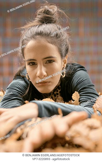confident woman laying on autumn leaves in city, content, focused emotion, Munich, Germany
