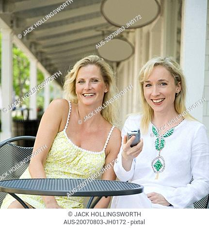 Portrait of a mature woman sitting in a cafe with a mid adult woman and smiling