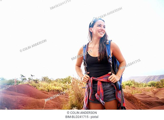 Smiling Caucasian woman hiking with backpack
