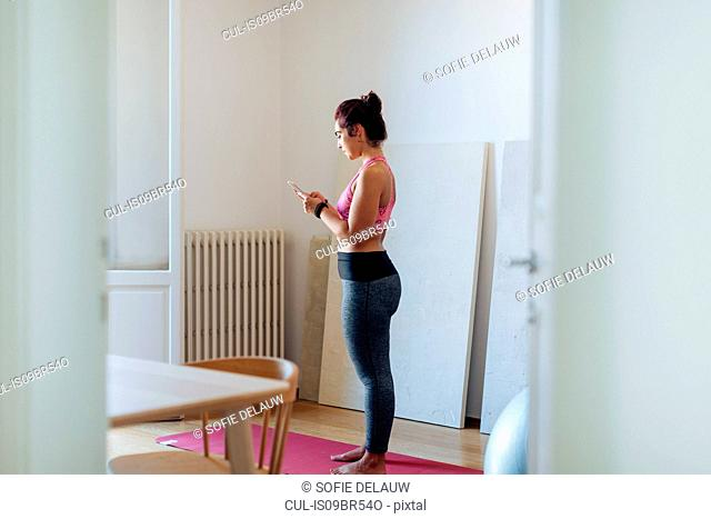 Woman doing exercise and texting at home