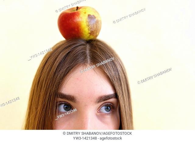 Portrait of beautiful brunette woman holding a red apple