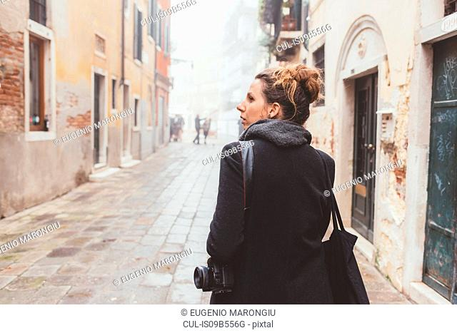 Young woman with camera looking over her shoulder on street, Venice, Italy