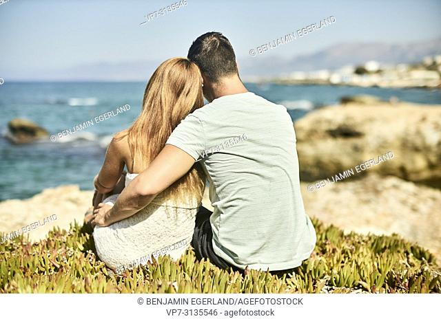 Rear view of couple in summer holiday, embracing, looking at view. Crete, Greece