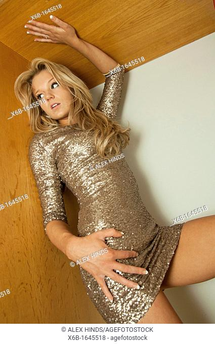 Young woman, 18-25 years, posing in gold sequin party dress