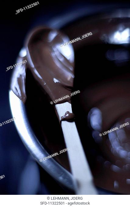 Melted chocolate in a bowl and on a spoon