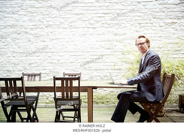 Businessman sitting at table in a backyard working with laptop