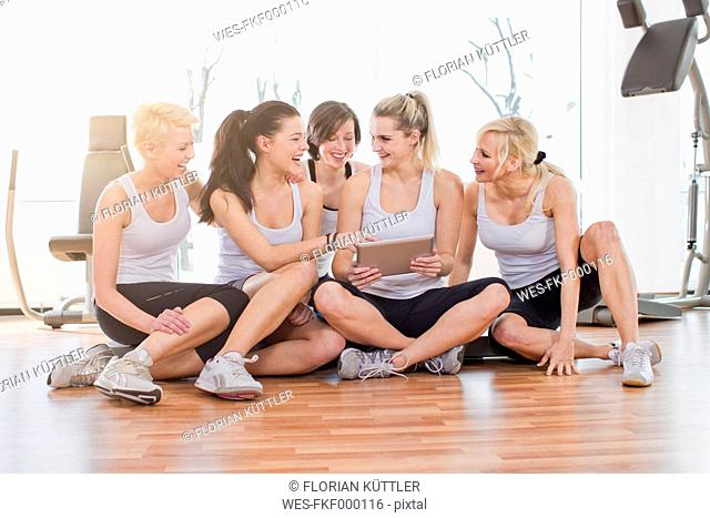 Germany, Brandenburg, Women using digital tablet in gym, smiling