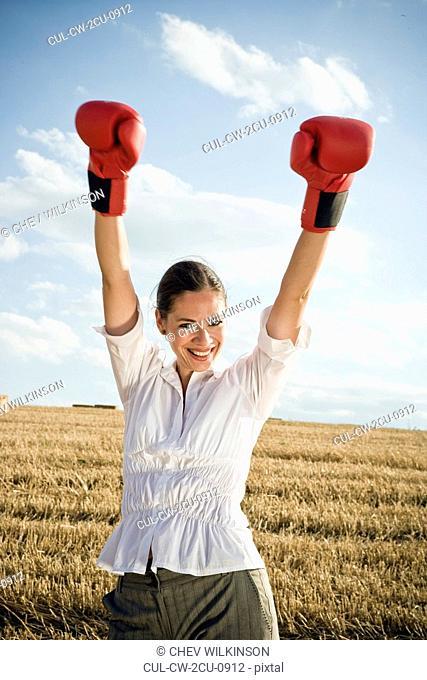 Businesswoman in wheat field wearing boxing gloves