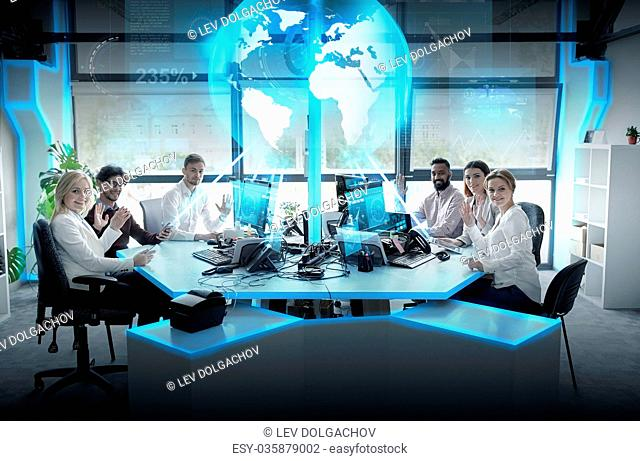 global network, technology and people concept - business team with computers waving hands at office