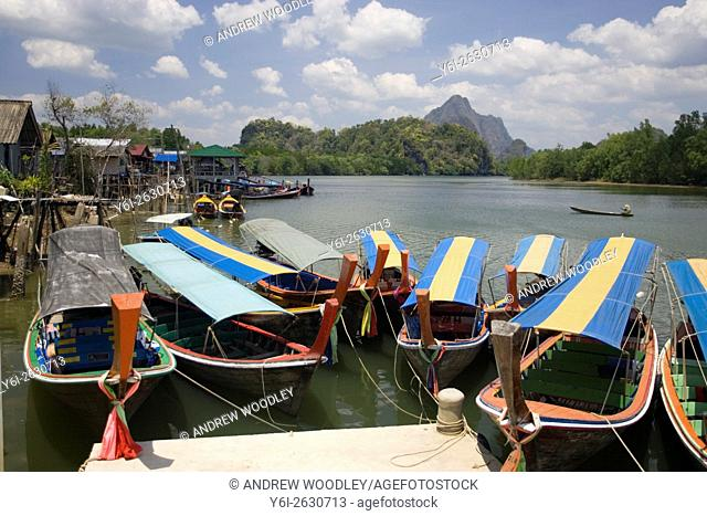 Covered tourist longtail boats for excursions into Phang Nga Bay Thailand
