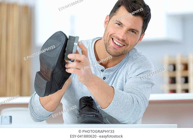 happy man brushing his shoes