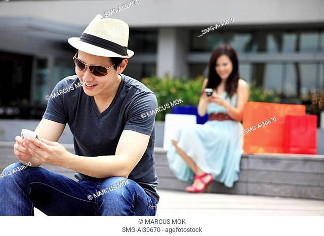Young man and woman sitting outdoors looking at phones