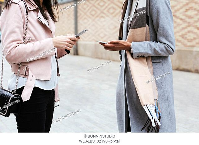Close-up of two women using cell phones in the city