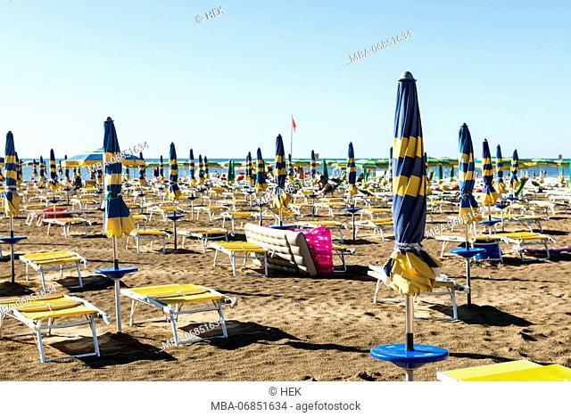 View of the sea through several rows of closed beach umbrellas, beach of Lignano