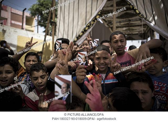 dpatop - Egyptian boys hold pictures of Egyptian President Abdel Fattah al-Sisi outside a polling station on the second day of the 2018 Egyptian presidential...