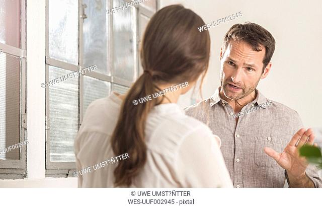 Businessman talking to woman in office