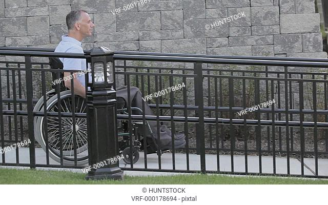 Man with spinal cord injury in a wheelchair using accessible wheelchair ramp slowly