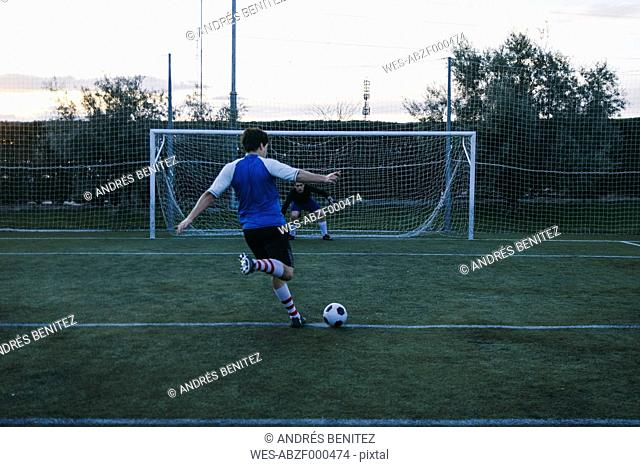 Football player kicking a ball in front of a goal with a goalkeeper
