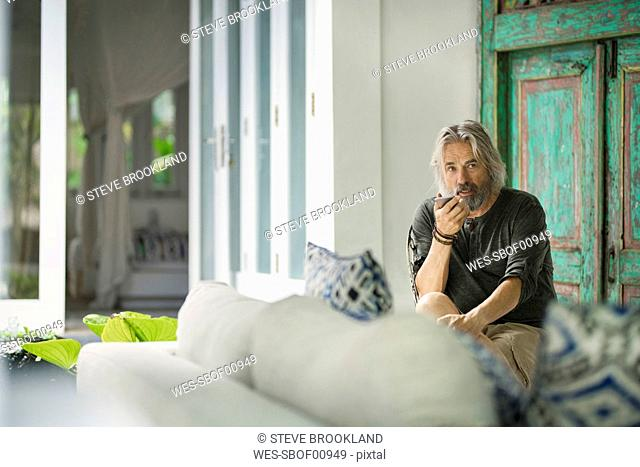 Senior man speaking on phone in his stylish home