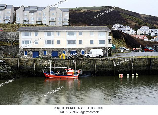 Fishing boat unloading lobster pots at the quayside using a crane, Aberystwyth, Wales, UK